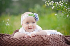 Charming child. Little girl with hat lying on her stomach Stock Image