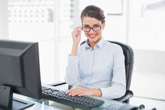 Charming classy brown haired businesswoman looking at camera over her glasses Royalty Free Stock Images