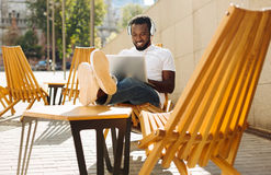 Charming clever man enjoying his day. Feeling the vibe. Friendly devoted hardworking guy visiting public place and using his computer while working outdoors Stock Images