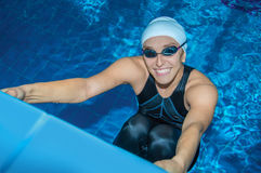Charming coach swims in the pool. And smiles Royalty Free Stock Image
