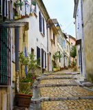 Charming, Colorful Street, Arles France. A quaint picturesque cobblestone street winds up a hill, with pots of bright flowers in pots, and colorful painted homes