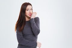 Charming confused woman with red lips biting nails. Charming confused young woman with red lips standing and biting nails over white background Royalty Free Stock Image