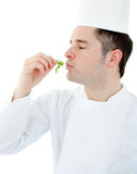 Charming cook with closed eyes holding a herb Royalty Free Stock Image