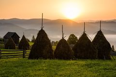 Beuatiful rural landscape in Bucovina, Romania. Charming countryside of Bucovina region in Romania with sunrise over the rolling hills filled in fog Stock Images