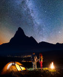 Charming couple backpackers holding hands, standing near campfire and enjoying starry sky Royalty Free Stock Photo
