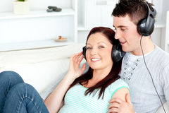 Charming couple listening to music with headphones. Lying on the sofa at home Royalty Free Stock Photo