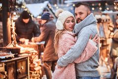 A charming couple in love, hugging together and looking at a camera while standing at the Christmas fair royalty free stock photo
