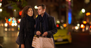 Charming couple shopping at night in big city Royalty Free Stock Photography