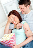 Charming couple on sofa with popcorn and remote Stock Photos