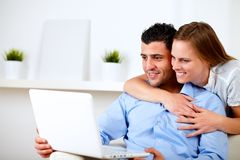 Charming couple using laptop together. Portrait of a charming couple using laptop together at living room at home indoor Royalty Free Stock Photo