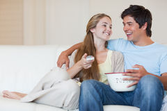 Charming couple watching television while eating popcorn royalty free stock photos