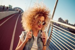 Charming curly blonde music lover. Young woman with big headphones. Royalty Free Stock Photos