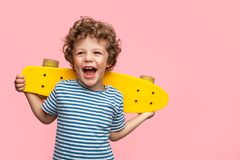 Cheerful boy with yellow longboard. Charming curly boy holding yellow longboard and looking away on pink background Royalty Free Stock Image