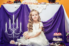 Charming curly girl posing in lush white dress Royalty Free Stock Photo