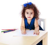 Charming curly little girl draws with markers Royalty Free Stock Photography