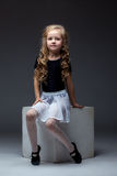 Charming curly performer posing in studio. On gray background Stock Photography