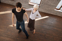 Charming dance teacher helping aging woman in the ballroom. Art challenge for my student. Flexible mature talented dance couch teaching elderly women tango while royalty free stock photography