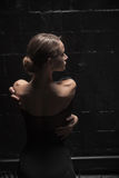 Charming dancer standing in full back position. Full of gracefulness .Charming graceful young dancer standing near the dark wall in a full back position and Royalty Free Stock Photos