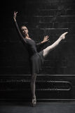 Charming dancer training near the black wall stock image