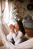 Charming dark-haired girl dressed in beige sweater and pants drinks from a red cup sitting in a hammock in a cozy stock photography
