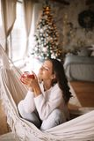 Charming dark-haired girl dressed in beige sweater and pants holds a red cup sitting in a hammock in a cozy decorated royalty free stock images
