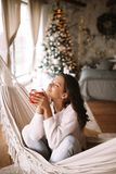 Charming dark-haired girl dressed in beige sweater and pants holds a red cup sitting in a hammock in a cozy decorated stock images