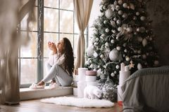 Charming dark-haired girl dressed in pants, sweater and warm slippers holds a red cup sitting on the windowsill of a royalty free stock image