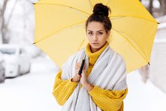 Charming dark-haired girl dressed in a yellow sweater, jeans and a white scarf is standing with a yellow umbrella in a royalty free stock photos