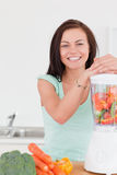 Charming dark haired woman posing with a blender Royalty Free Stock Photography