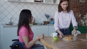 Charming disabled female her casual clothes sitting comfort handicap house. With bright and natural daylight in the room. Adult woman in wheelchair making stock footage