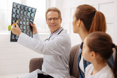 Charming doctor having some good news for his clients. You made some progress. Experienced charming professional surgeon sharing some nice information with stock images