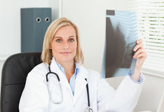 Charming doctor holding x-ray looks into camera Royalty Free Stock Photo