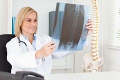Charming doctor looking at x-ray. In her office Royalty Free Stock Photo
