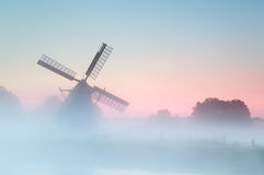 Charming Dutch windmill in dense sunrise fog Stock Images