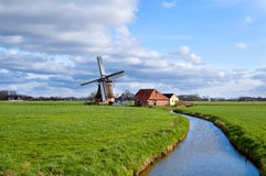 Charming dutch windmill on green grasslands Royalty Free Stock Images