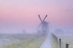 Charming Dutch windmill in morning mist Royalty Free Stock Photography