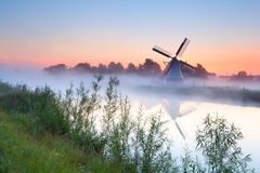 Charming Dutch windmill by river Stock Images