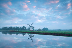 Charming Dutch windmill by river during sunrise Royalty Free Stock Images