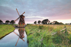 Charming Dutch windmill by river at sunrise Royalty Free Stock Image