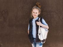 Charming eight-year-old girl in a trendy outfit with a backpack standing on the street on a sunny day.  stock photos