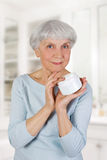 Charming elderly woman applying cosmetic cream on her face for facial skin care in bathroom at home Royalty Free Stock Photo