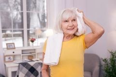 Charming elderly woman towel-drying her hair after workout stock photo