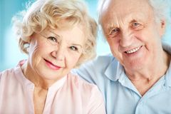 Charming elders. Close-up portrait of a charming elder couple looking at the viewer with a smile stock photo