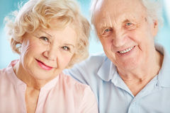 Charming elders. Close-up portrait of a charming elder couple looking at the viewer with a smile royalty free stock photo