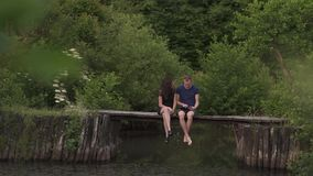 Charming elegant couple sitting on a wooden pontoon on a river in summertime and using a digital tablet stock video