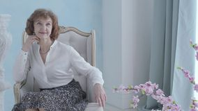 Portrait charming elegant mature woman in white blouse sitting in the armchair smiling. The unrecognizable man standing. Charming elegant mature woman in white stock video