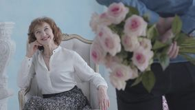 Portrait beautiful cute elegant mature woman in white blouse sitting in the armchair smiling. The unrecognizable man. Charming elegant mature woman in white stock video