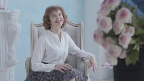 Charming elegant mature woman in white blouse sitting in the armchair smiling. The unrecognizable man standing with his. Back to camera holding bouquet of pink stock video footage