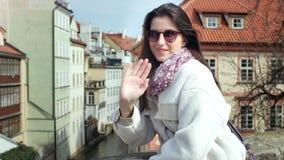 Charming elegant tourist woman waving hand enjoying view on narrow water canal from balcony