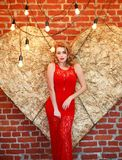 Charming woman in red dress on golden heart in studio. Charming elegant woman in a red dress on a background of a golden heart in the studio Stock Photography